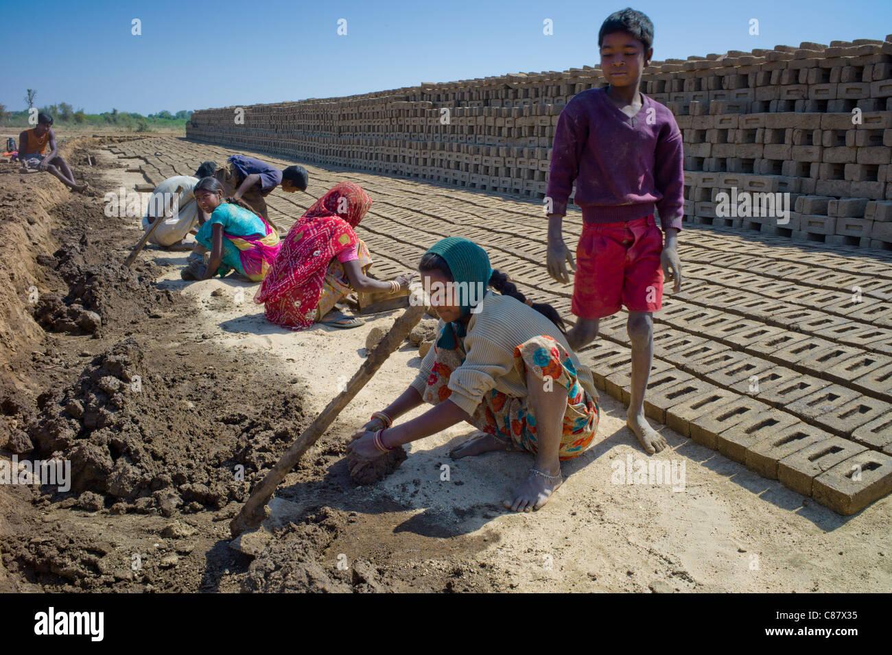 Indian family making bricks made from mud clay at Khore Bricks Factory, Rajasthan, Northern India - Stock Image