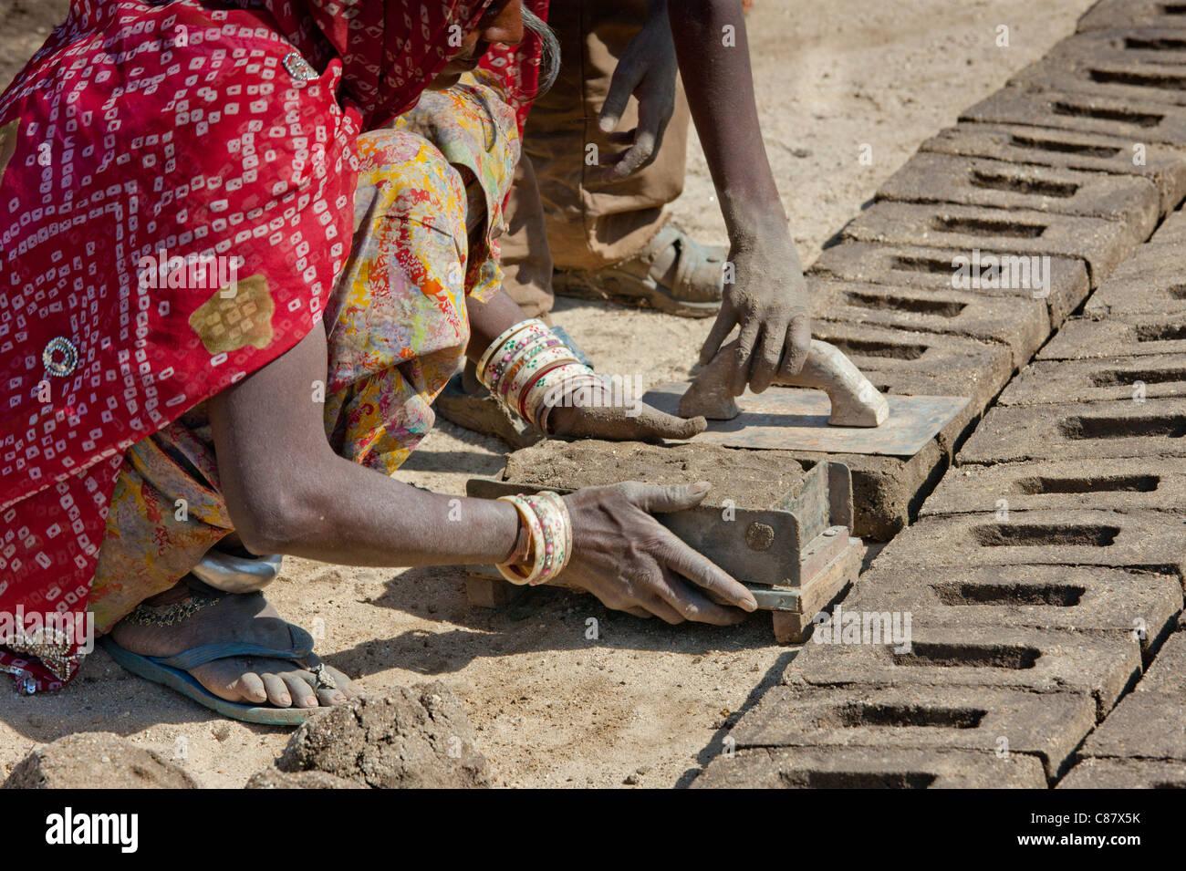 Indian family forming bricks made from mud clay at Khore Bricks Factory, Rajasthan, Northern India - Stock Image