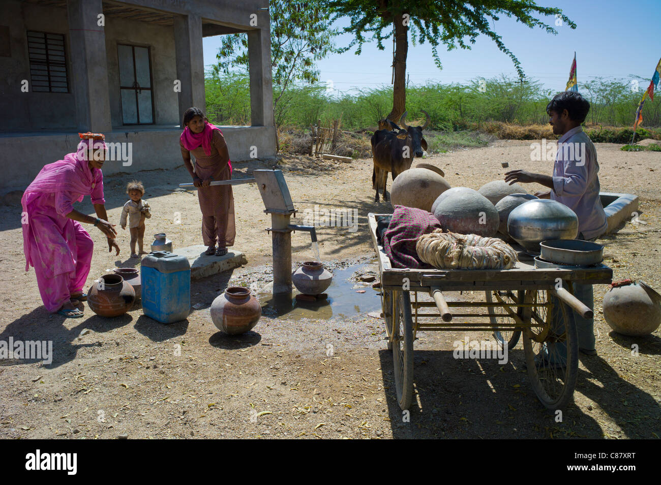 Indian women in sari fetching water pot from well at Jawali village in Rajasthan, Northern India - Stock Image