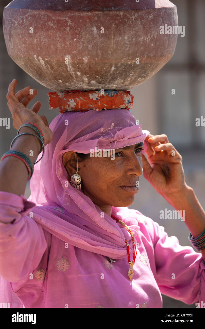 Indian woman in sari fetching water pots from well at Jawali village in Rajasthan, Northern India - Stock Image