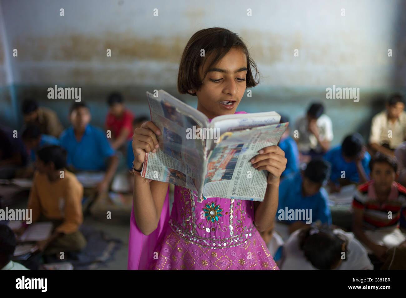 Indian girl reading aloud during English lesson at Rajyakaiya School in Narlai village, Rajasthan, Northern India - Stock Image