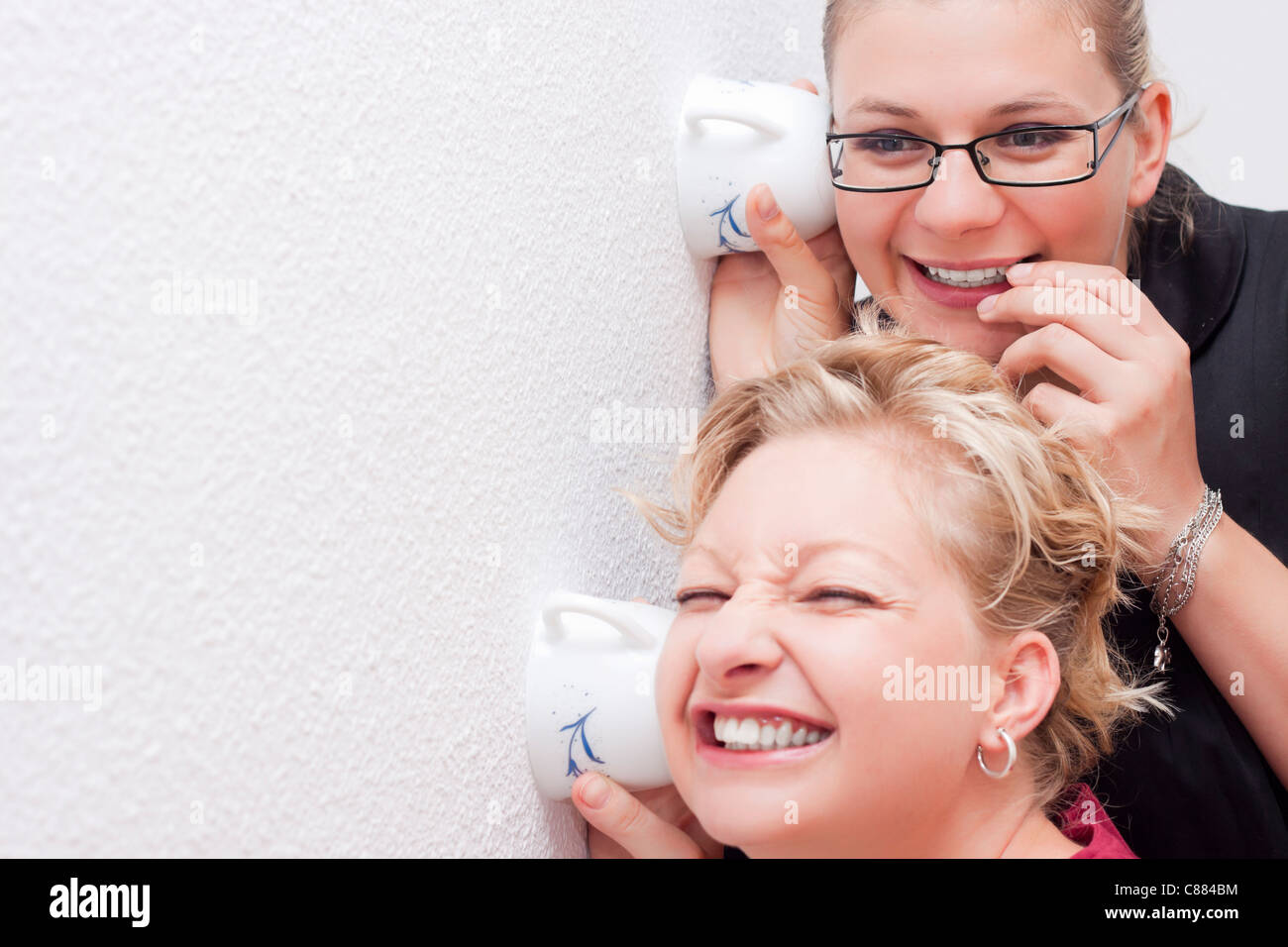 Funny moment of two young women spying. - Stock Image
