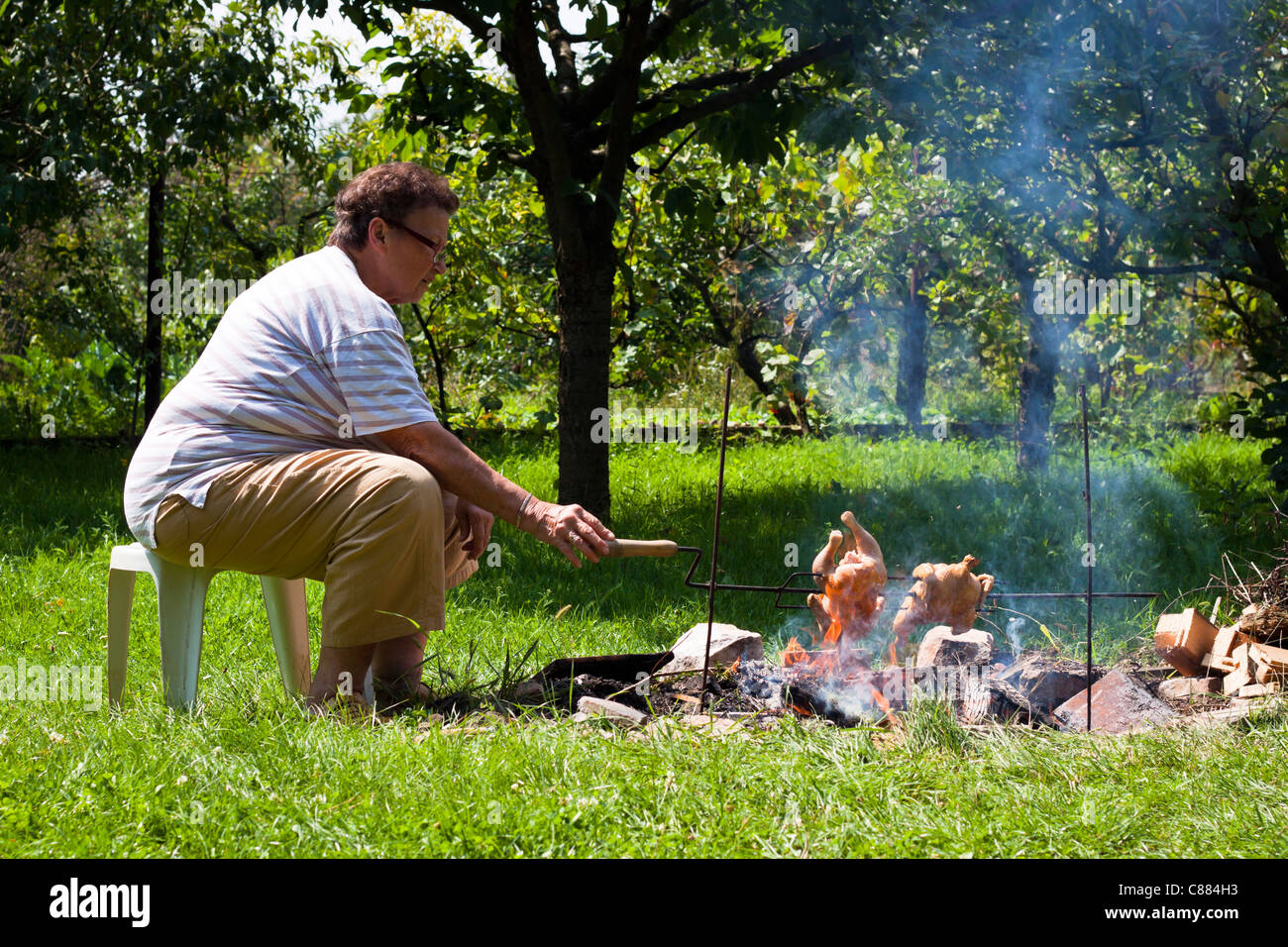 Senior woman grilling chickens on bonfire. - Stock Image