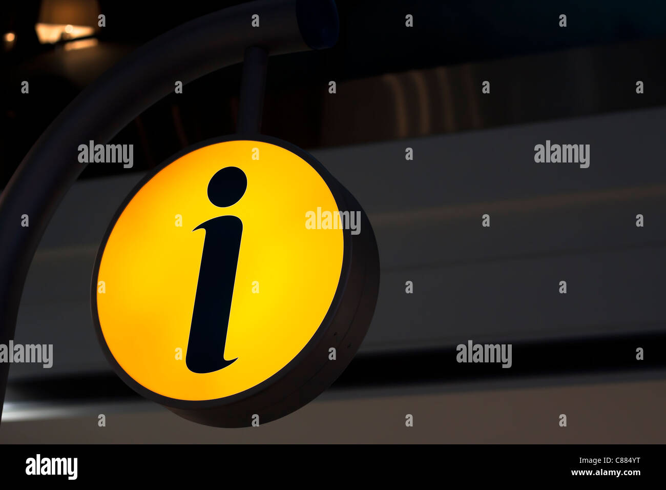 Glowing sign on dark background with the letter i as a symbol for information. - Stock Image