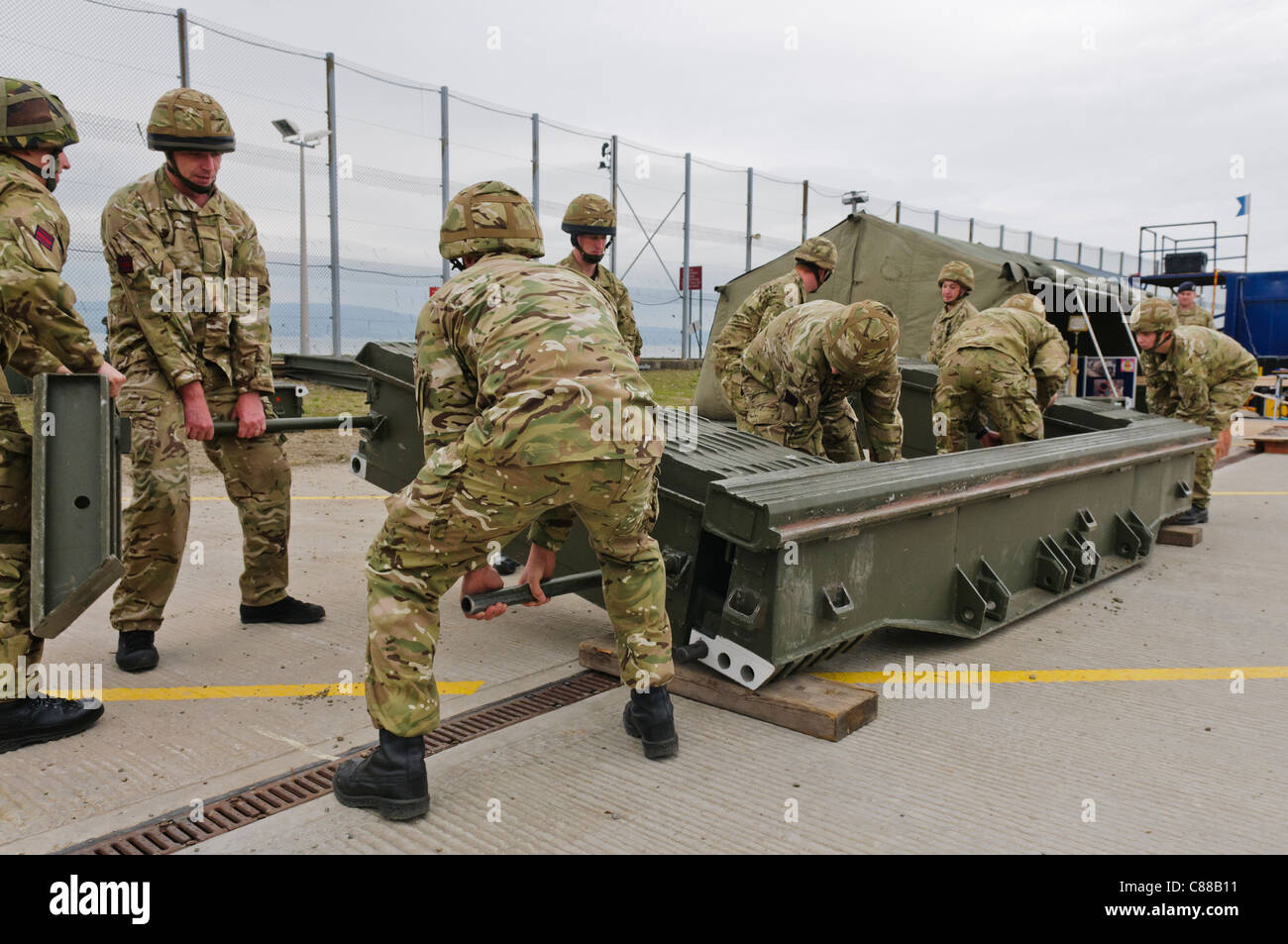 Soldiers assemble a mobile pontoon for crossing gaps - Stock Image