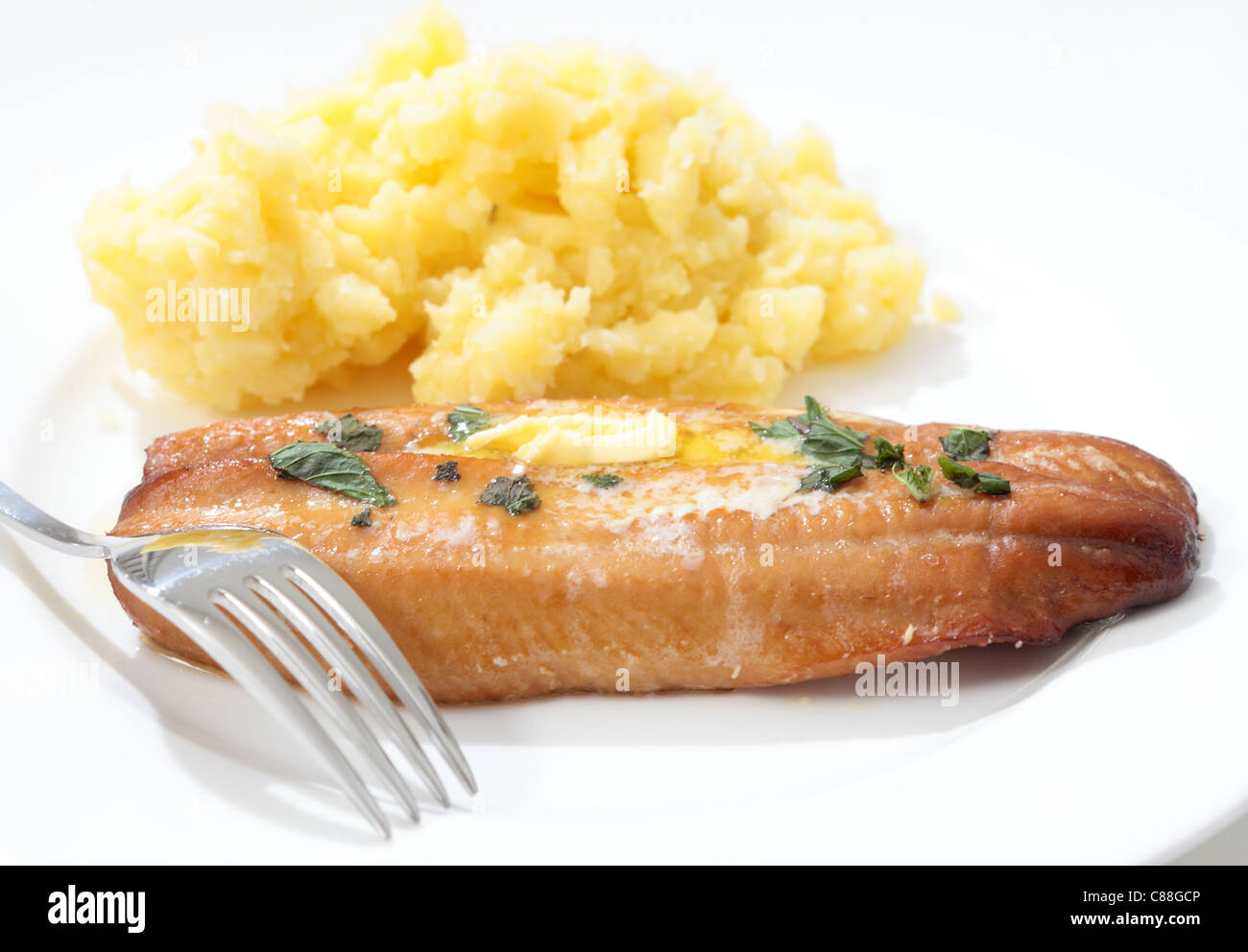 A grilled kipper garnished with herbs and a dab of butter, served with mashed boiled potatoes - Stock Image