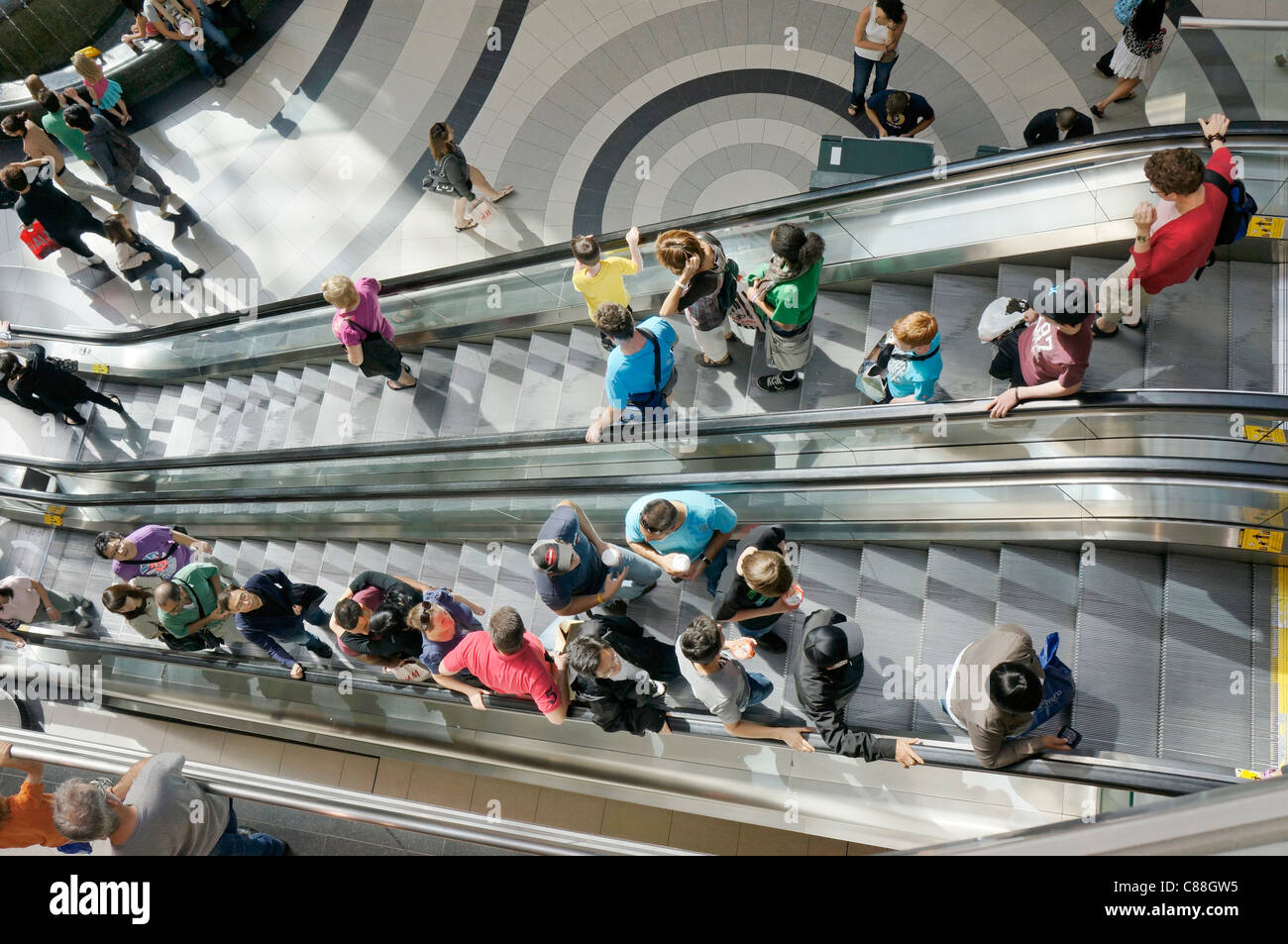 People on escalators in shopping mall - Stock Image