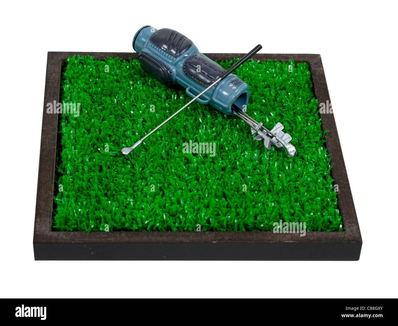 Golf bag used to carry the clubs and balls used during the game laying on green grass - path included - Stock Image