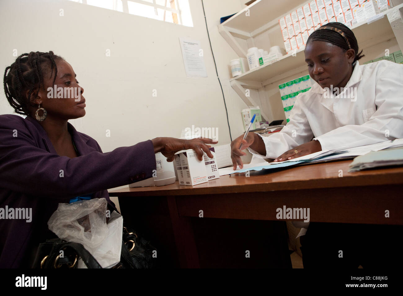 A pharmacist distributes ARV drugs to an HIV positive patient at a Catholic Relief Services-supported clinic in - Stock Image