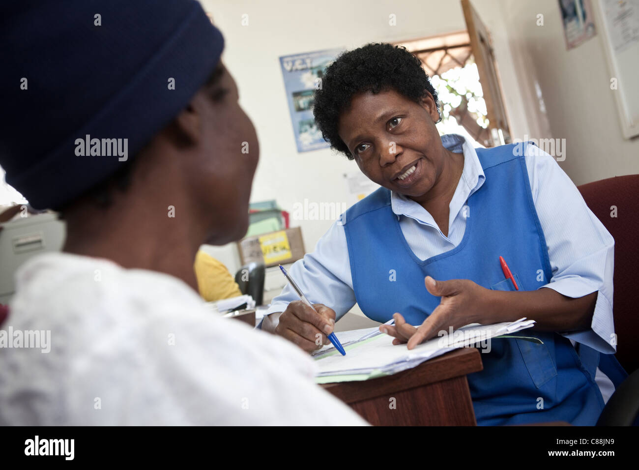 A nurse consults with an HIV positive patient in an AIDS Relief clinic supported by Catholic Relief Services in Stock Photo