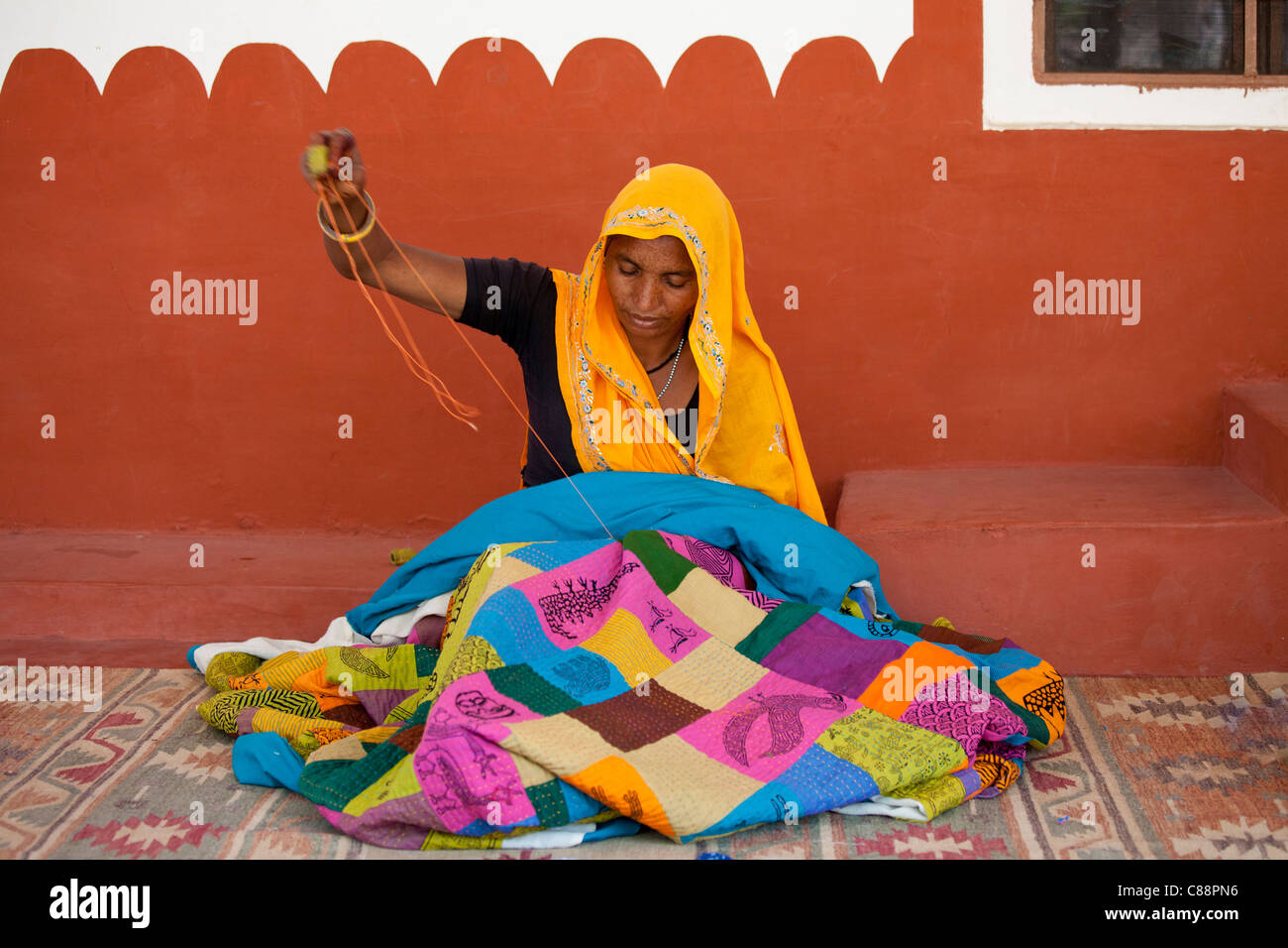 Indian woman sewing textiles at Dastkar women's craft co-operative, the Ranthambore Artisan Project, in Rajasthan, - Stock Image