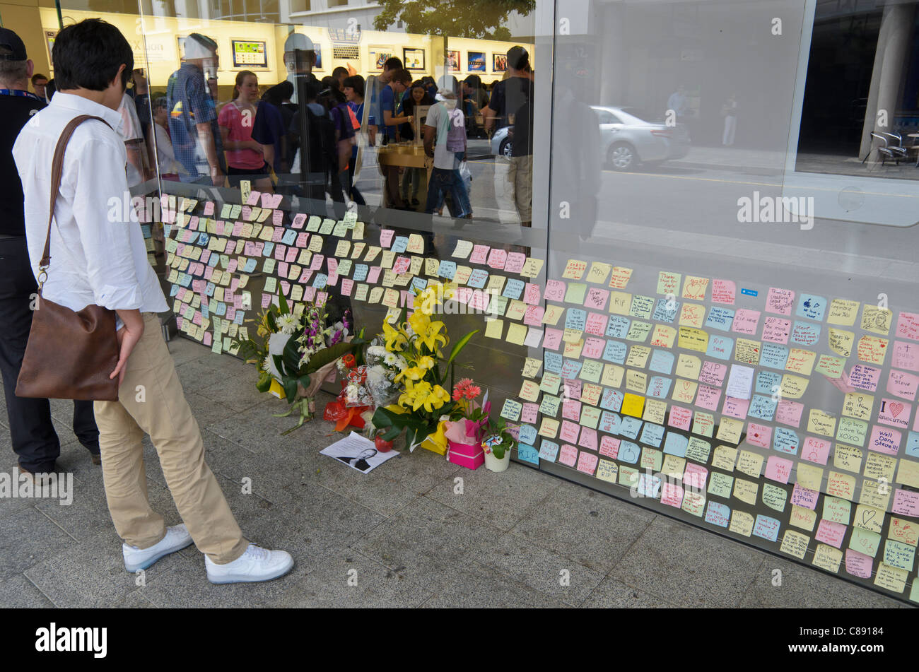 A man looks at the post-it note tributes on the window of an Apple Store in Perth, Western Australia - Stock Image
