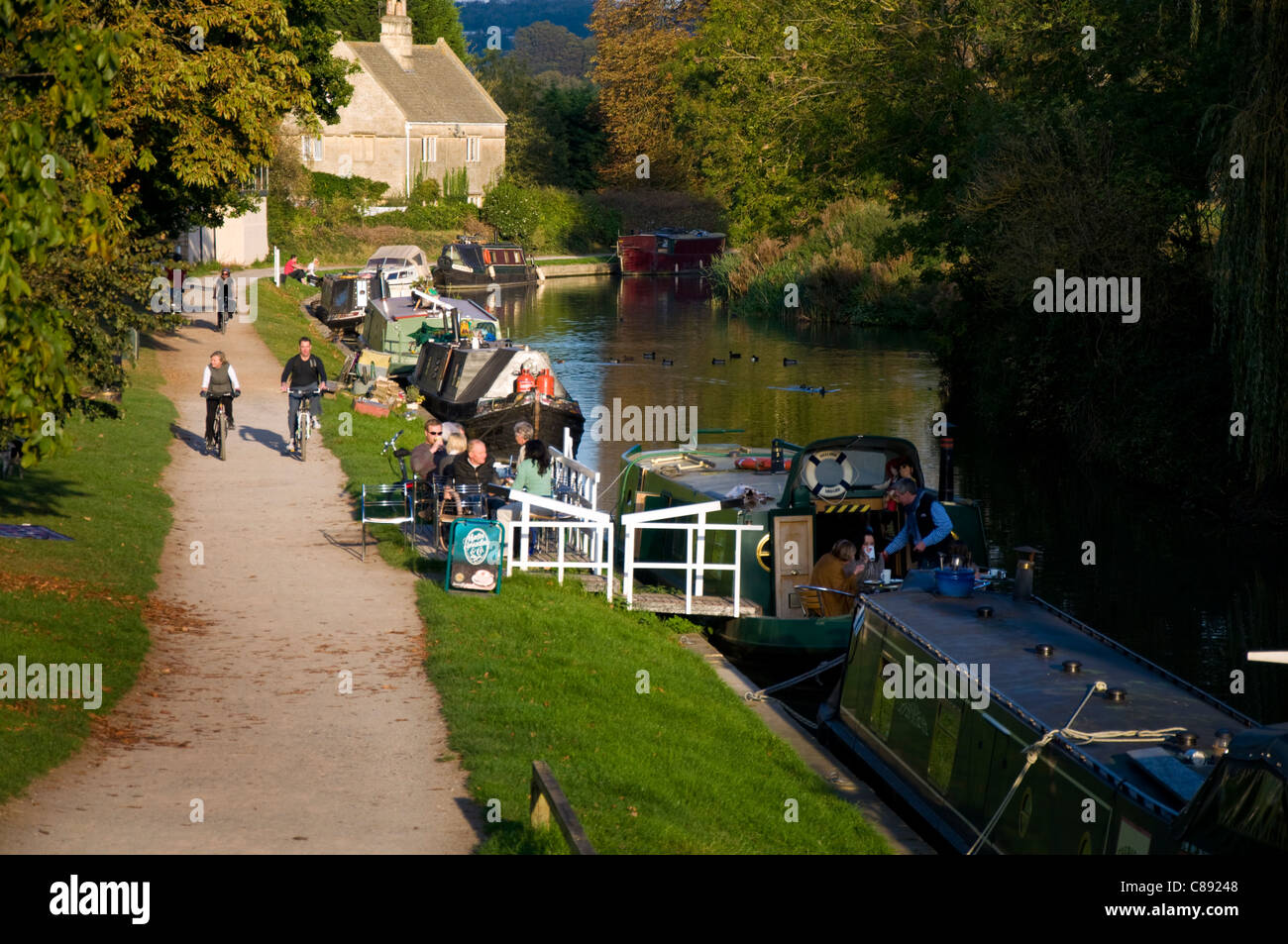 People enjoy coffee on by the Raft Cafe Boat the Kennet and Avon Canal at Bathampton - Stock Image