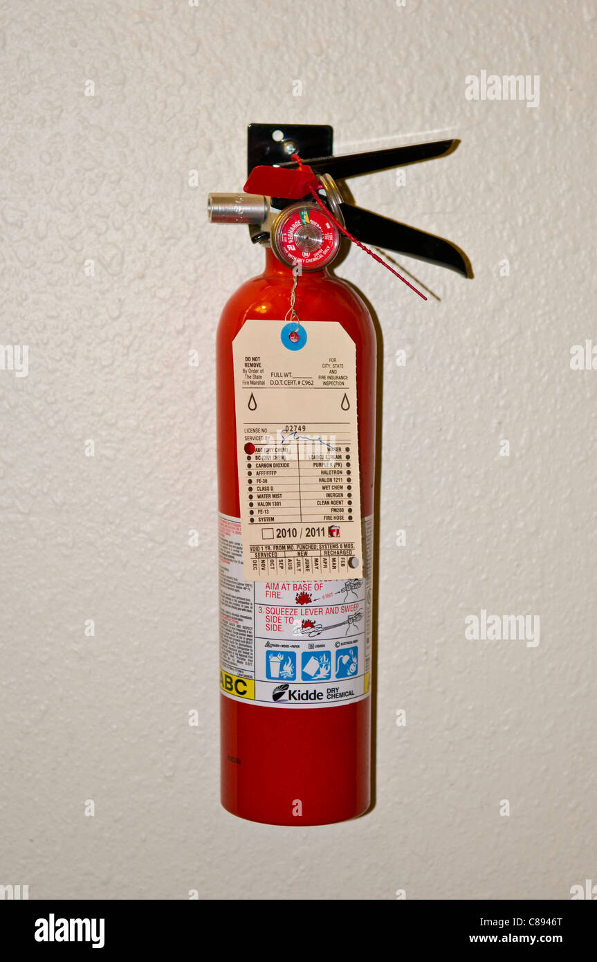 Red portable home fire extinguisher mounted on wall - Stock Image
