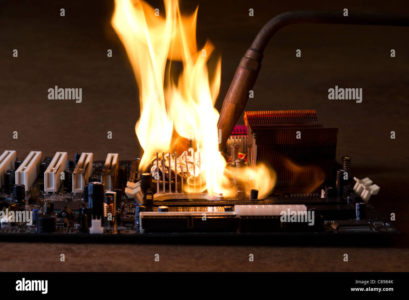 burning computer main board in rusty background. Copyspace Stock Photo