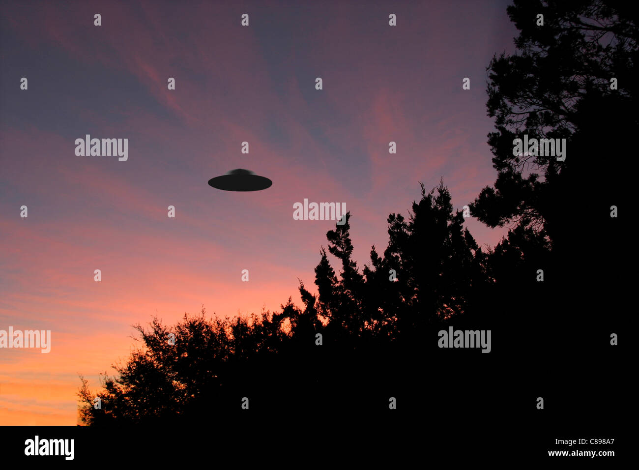 Sinister looking UFO silhouettes against sunrise - Stock Image