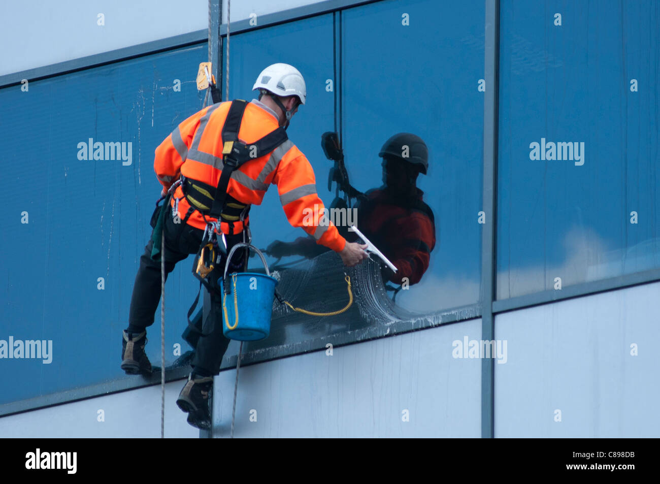 A window cleaner at work on an office building in Birmingham, UK. - Stock Image