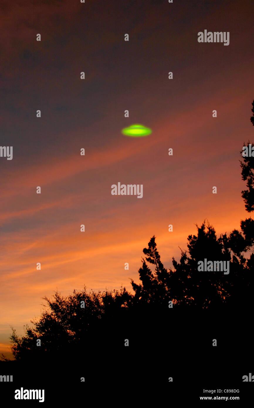 Glowing green UFO at sunrise - Stock Image