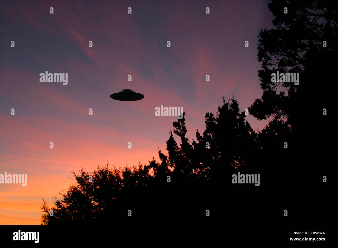 Sinister looking UFO at sunrise - Stock Image
