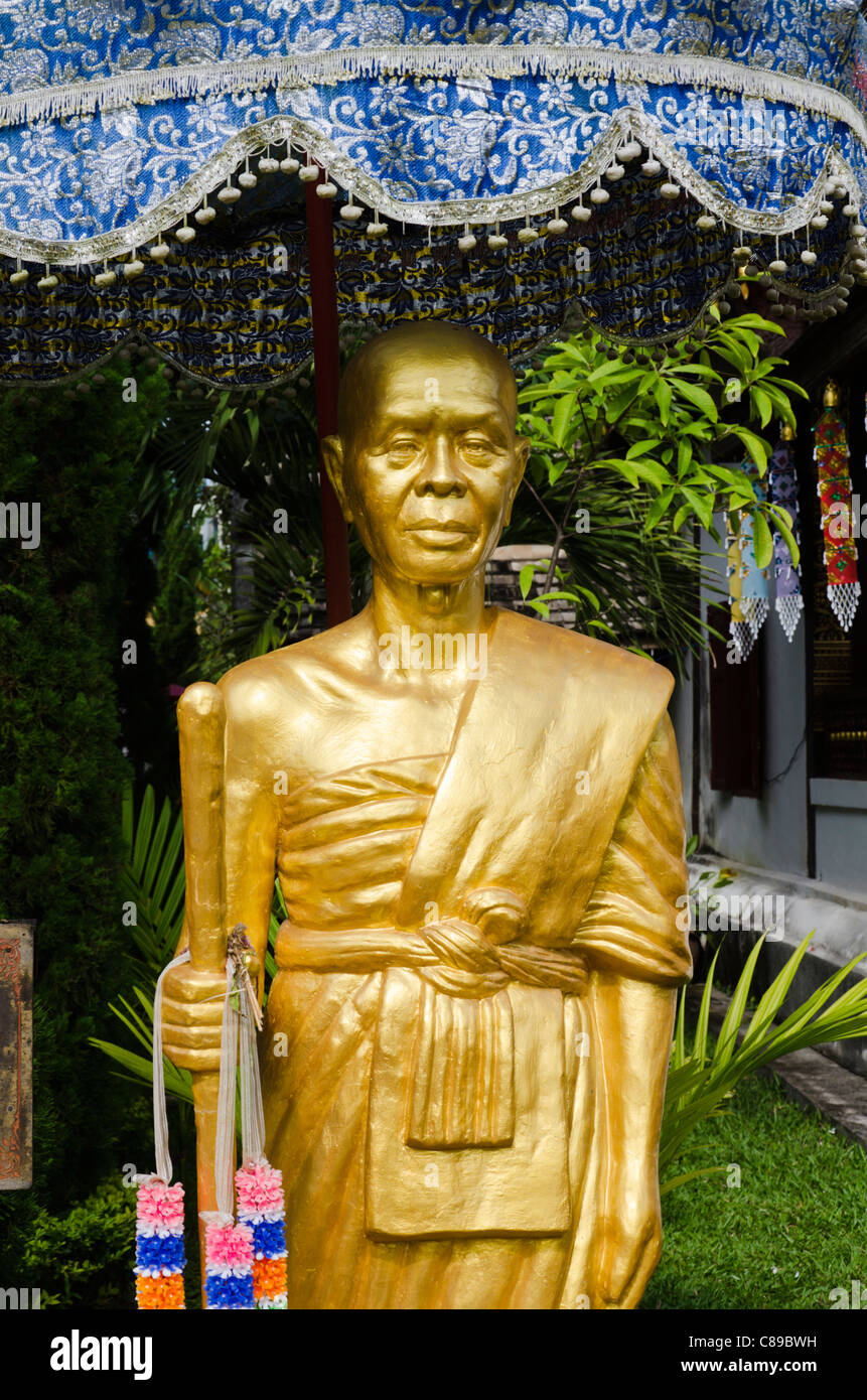 Gold statue of highly revered Buddhist saint Phra Kru Ba Sri Vichai of the North at Buddhist temple near Chiang - Stock Image