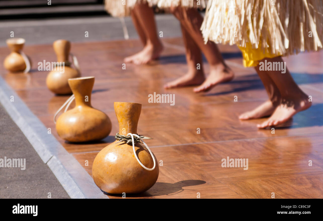 Hula gourds lined up in front of Hawaiian dancers - Stock Image
