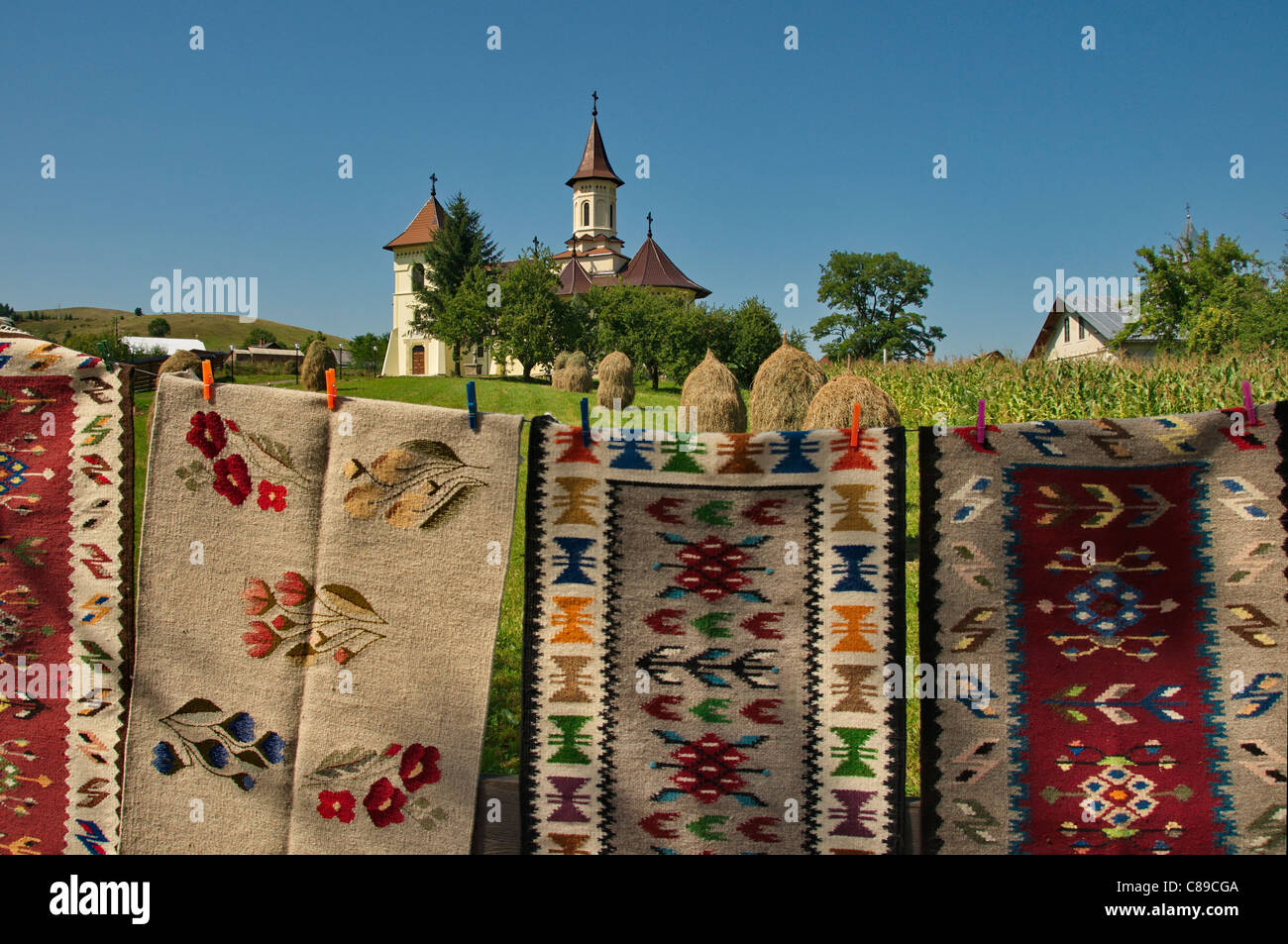 Traditional landscape of a church and handmade carpets in Moldova, Romania - Stock Image