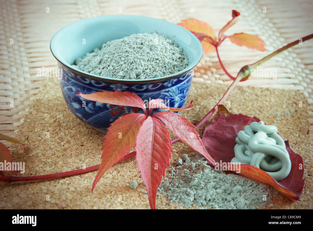 porcelain drinking bowl with powder of cosmetic blue clay - Stock Image