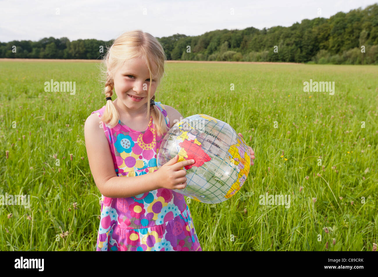 Germany, North Rhine-Westphalia, Hennef, Girl standing with beach ball globe in meadow Stock Photo
