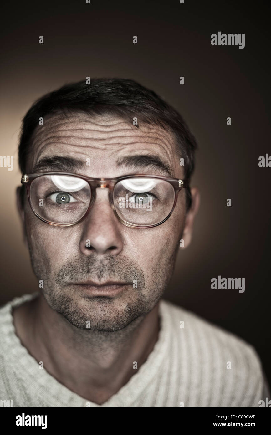 Close up of mature man making funny faces against black background, portrait - Stock Image