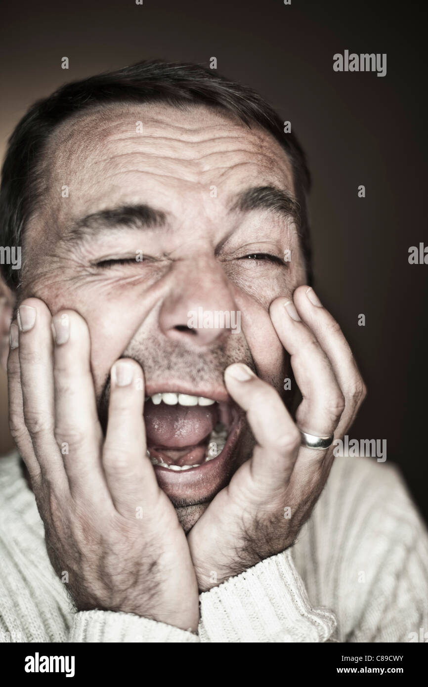 Close up of mature man making funny faces against black background - Stock Image