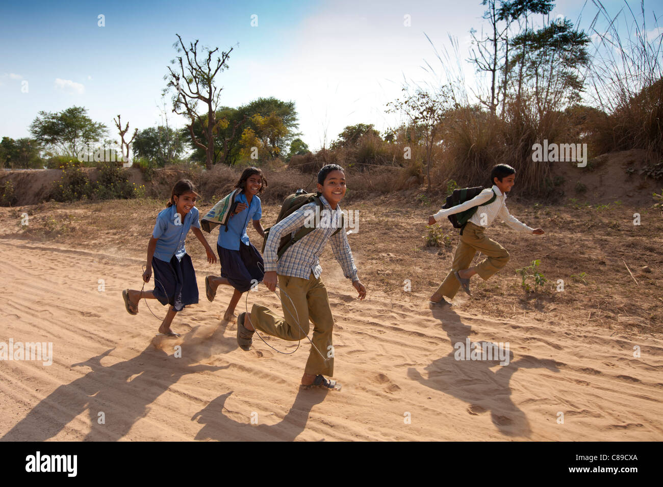 Indian schoolboys and girls walking to school at Doeli in Sawai Madhopur, Rajasthan, Northern India - Stock Image