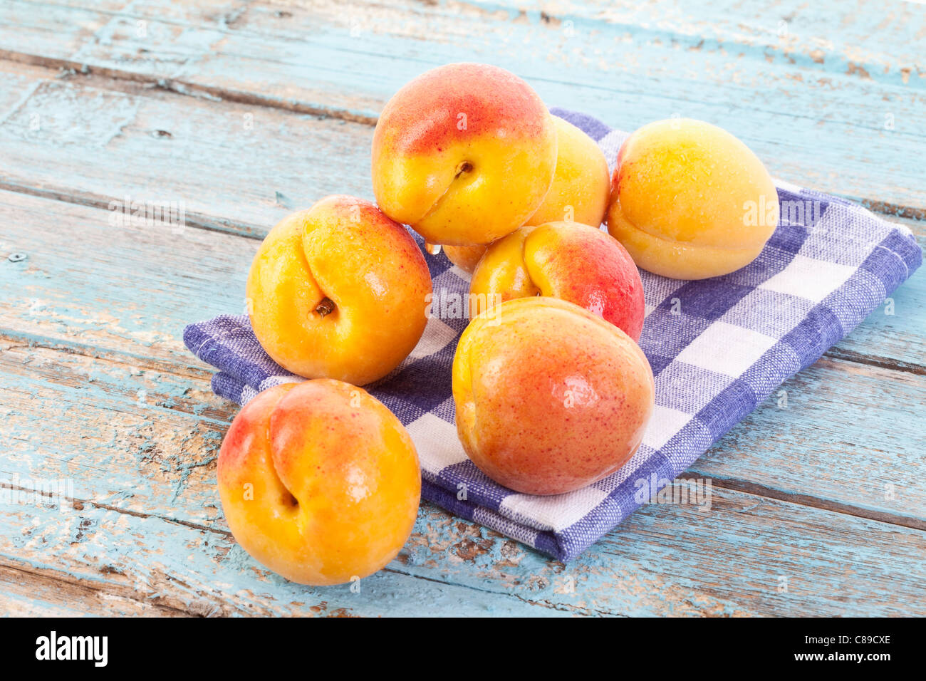 Close up of apricots on checked napkin - Stock Image