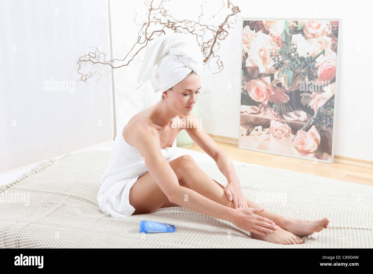 Young woman wrapped in towel applying body cream - Stock Image