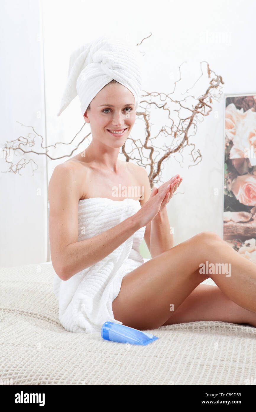 Young woman wrapped in towel rubbing body cream - Stock Image