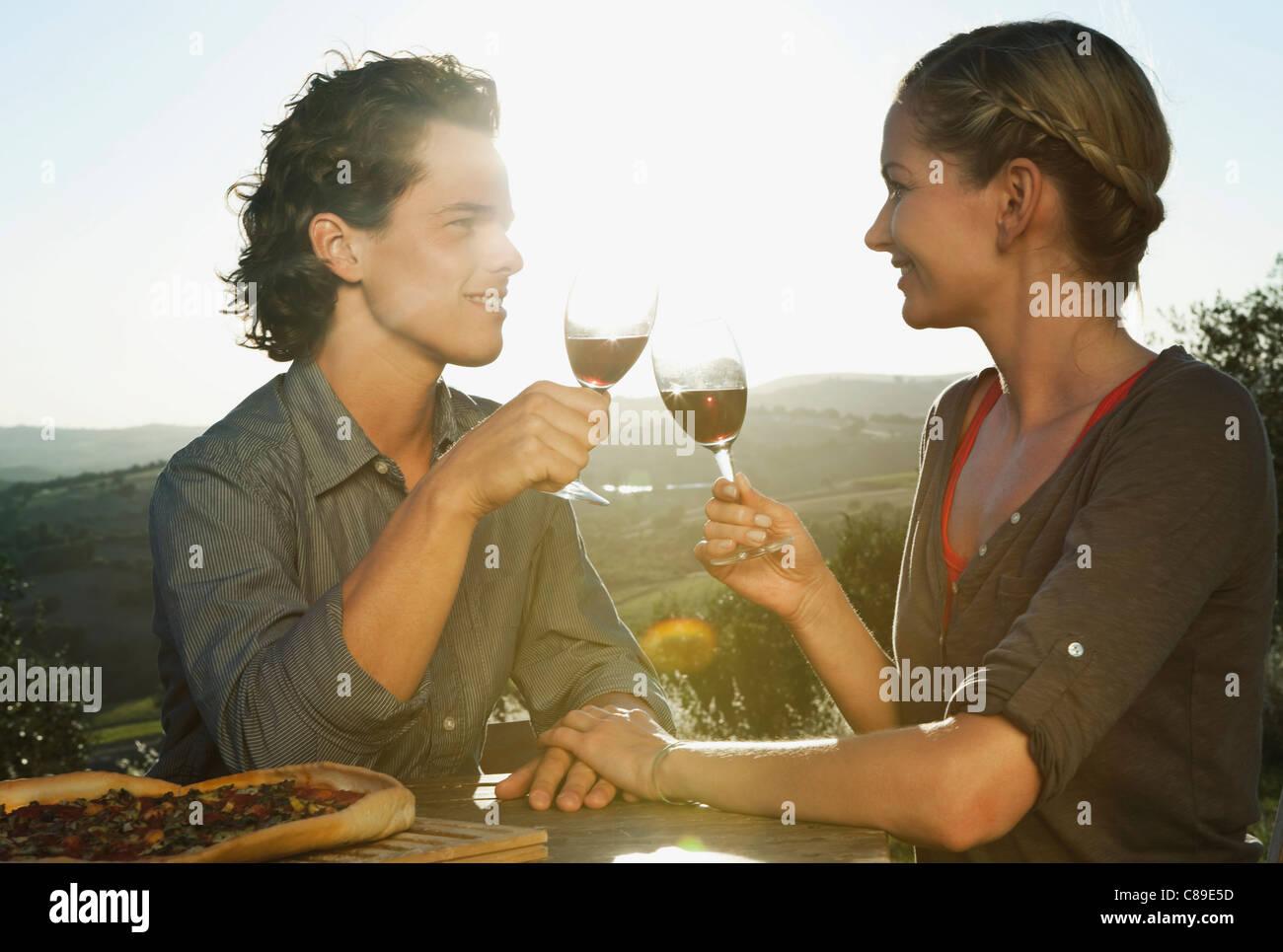 Italy, Tuscany, Young couple clinking wine glasses at dusk - Stock Image