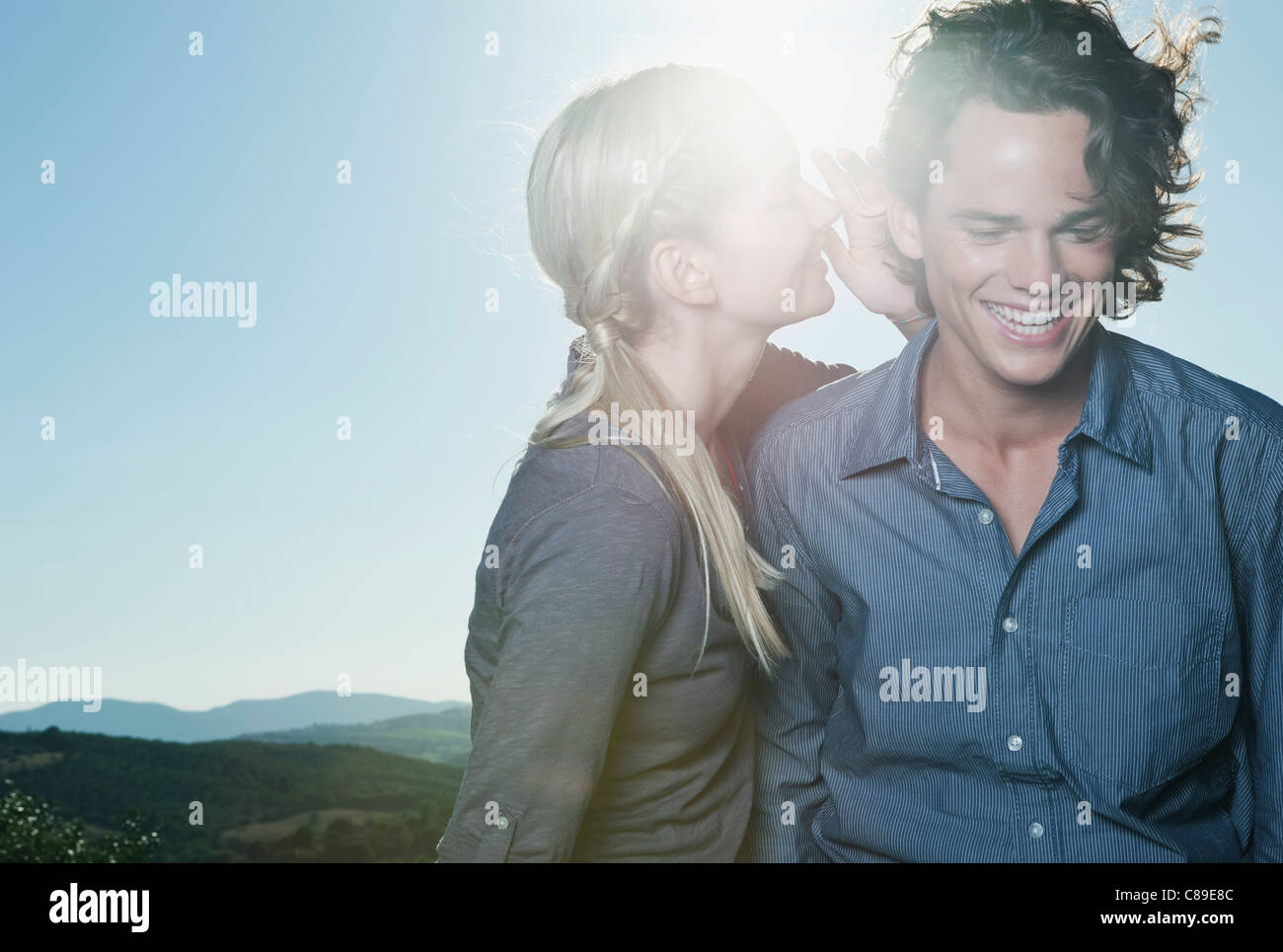 Italy, Tuscany, Young woman whispering in man's ear against sun - Stock Image
