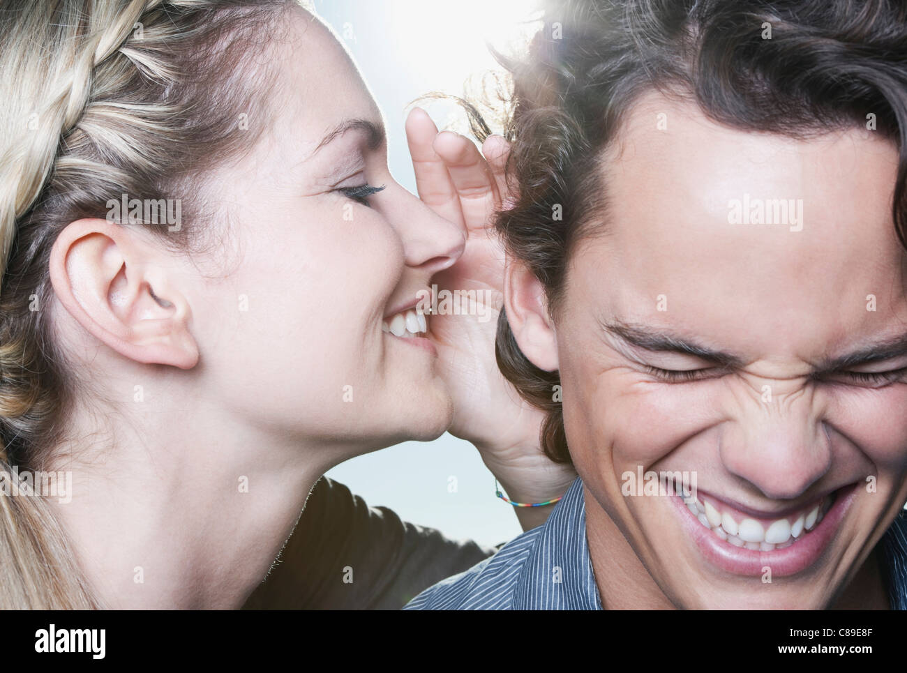 Italy, Tuscany, Young woman whispering in man's ear, close up - Stock Image