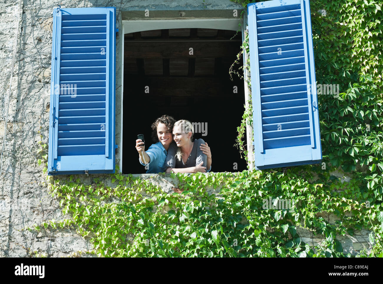 Italy, Tuscany, Young couple photographing at hotel windows with shutter - Stock Image