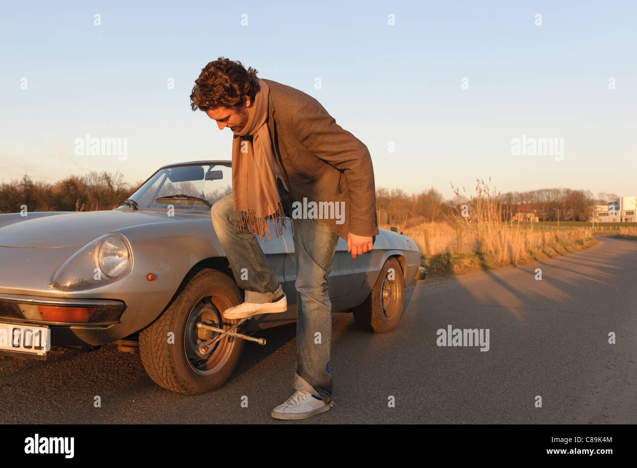 Germany, Hamburg, Man changing tyre of classic cabriolet car Stock Photo