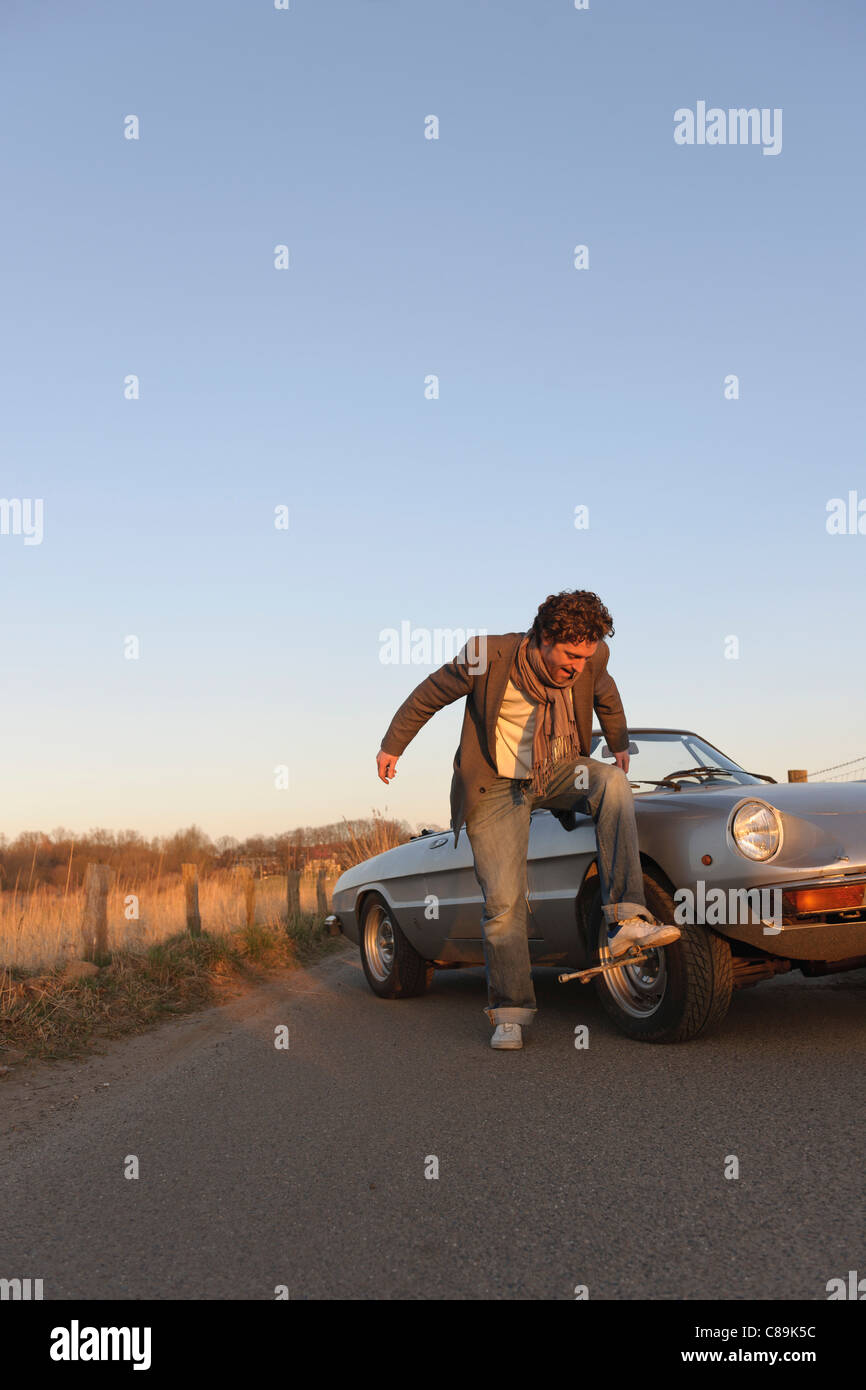Germany, Hamburg, Man changing tyre of classic cabriolet car - Stock Image