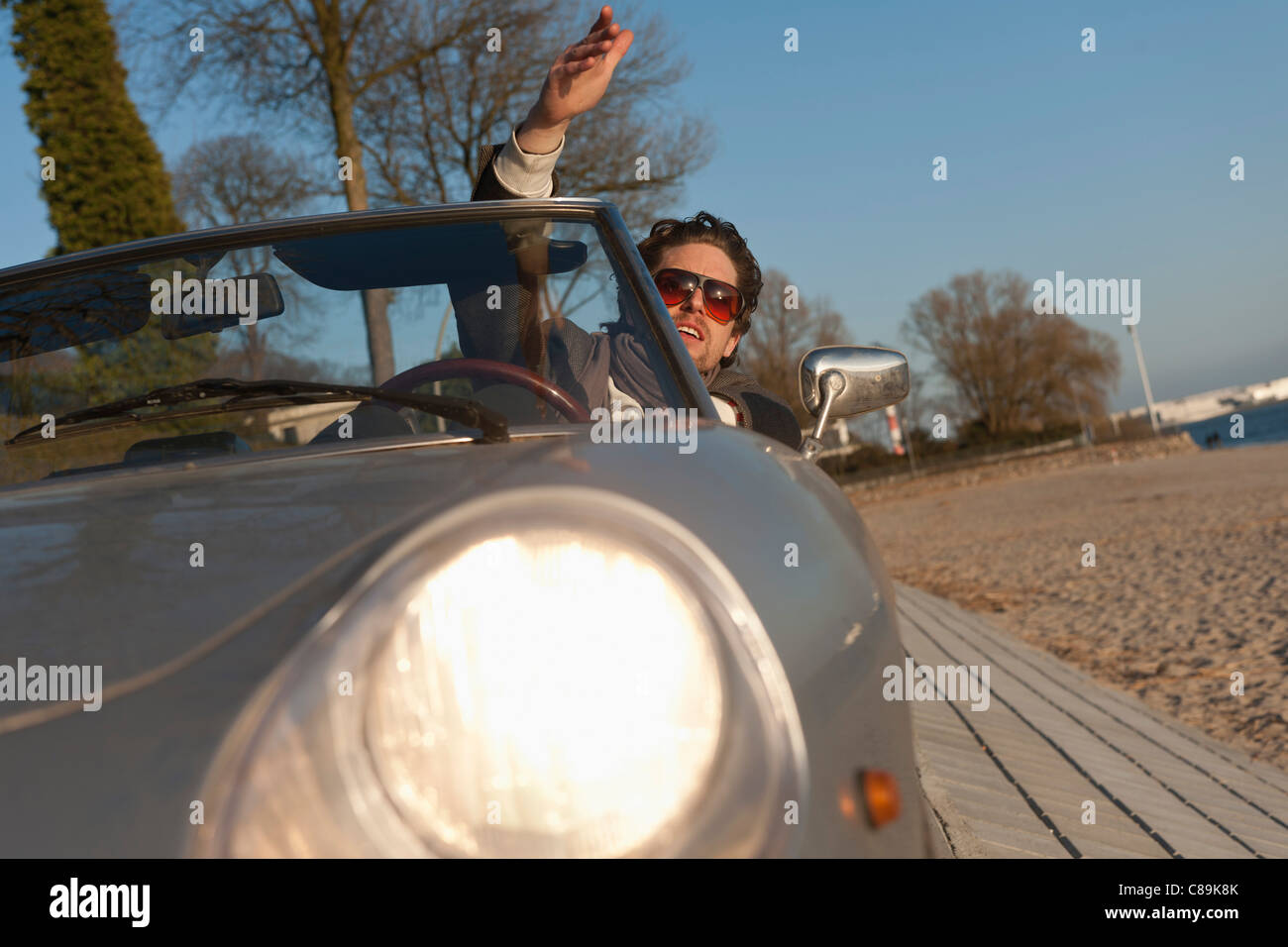 Germany, Hamburg, Man driving classic cabriolet car - Stock Image