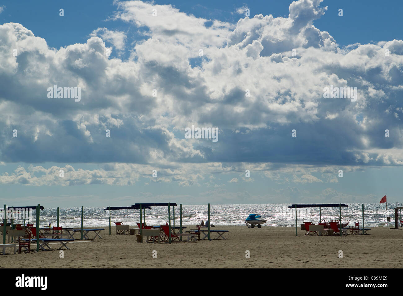 Italy, Forte dei Marmi, View of sandy beach with blue sky and white dense clouds - Stock Image