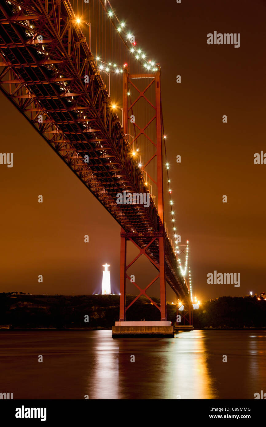 Europe, Portugal, Lisbon, View of suspension bridge with river Tagus at night - Stock Image