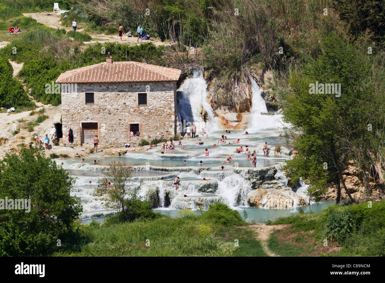 Italy, Tuscany, Province of Grosseto, Saturnia, View of people at thermal waterfalls and travertine pool - Stock Image