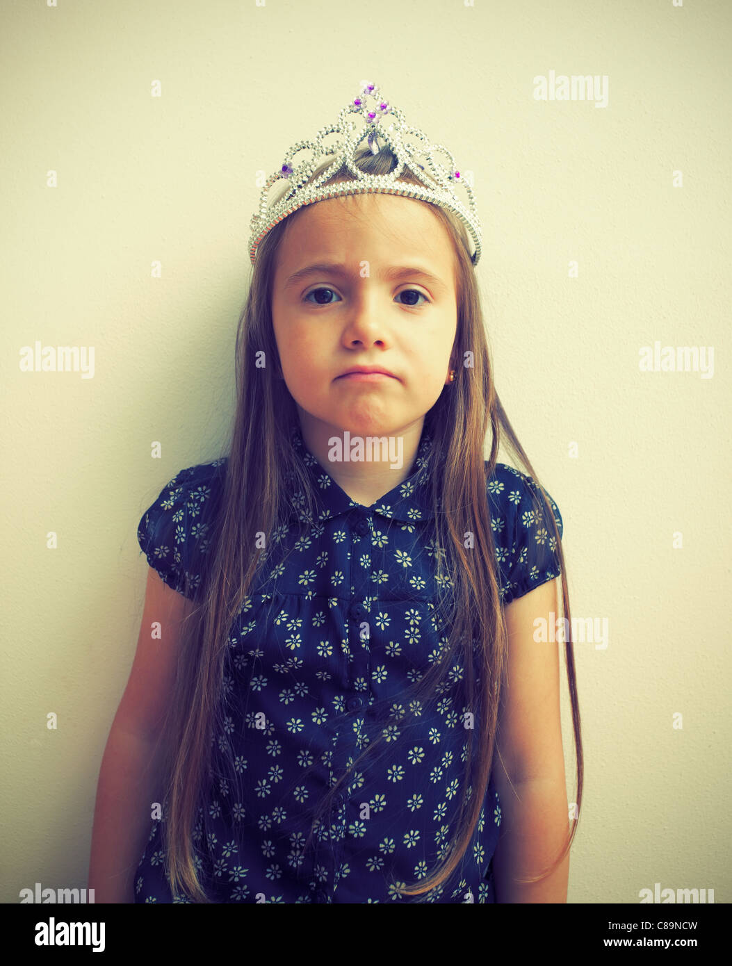 Cross-processed portrait of an ordinary girl with toy crown on her head - Stock Image