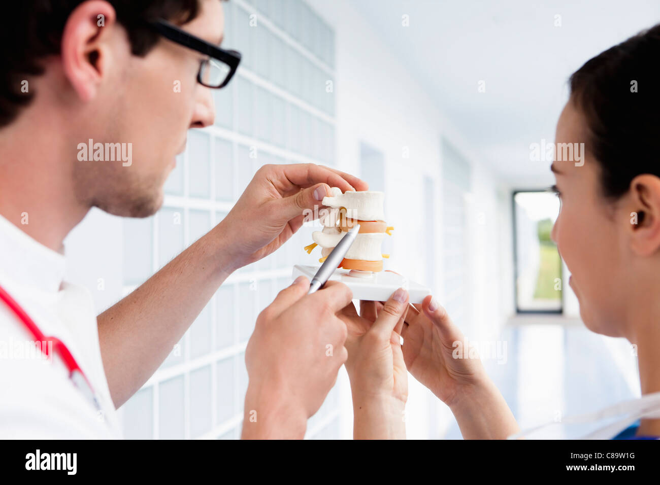 Germany, Bavaria, Diessen am Ammersee, Two young doctors examining medical procedure - Stock Image