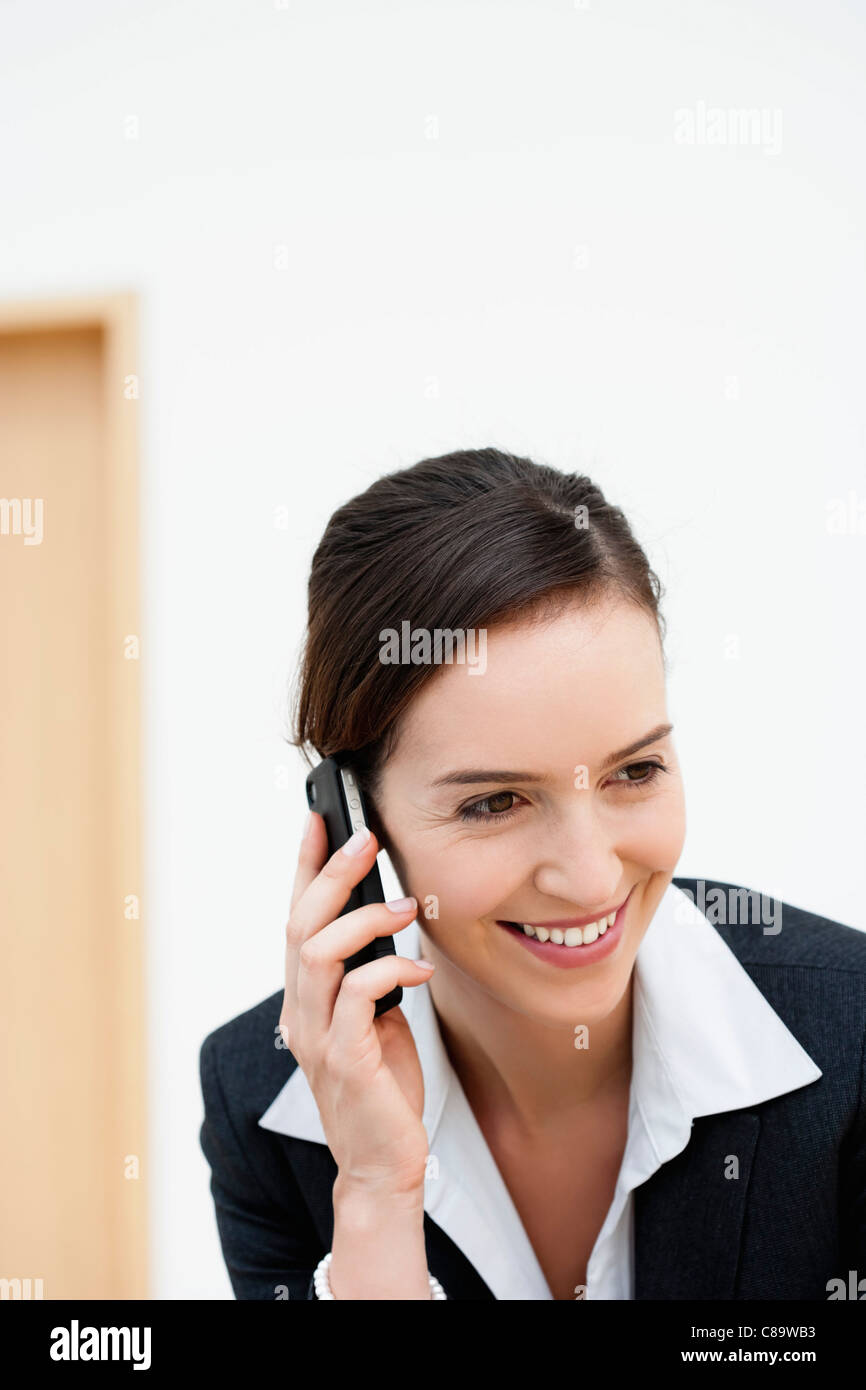 Germany, Bavaria, Diessen am Ammersee, Young businesswoman talking on mobile phone, smiling - Stock Image