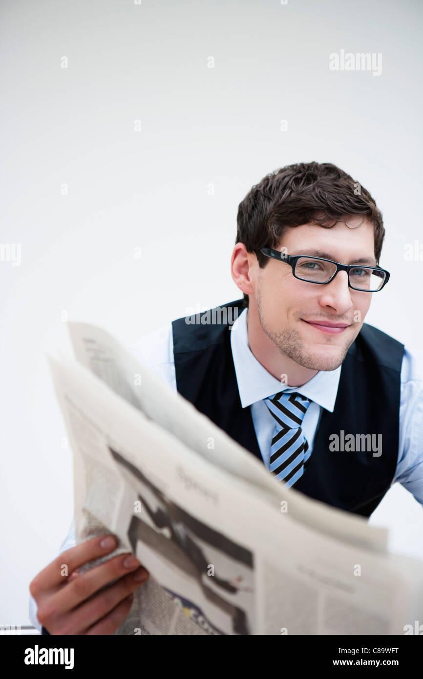 Germany, Bavaria, Diessen am Ammersee, Businessman holding newspaper, smiling, portrait - Stock Image