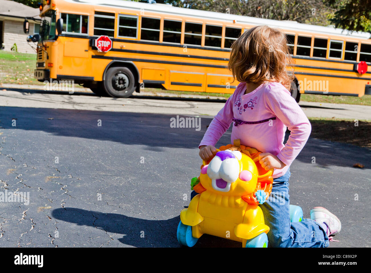 A four and a half year old little girl sits on a riding toy in her driveway turns to look at a yellow school bus Stock Photo