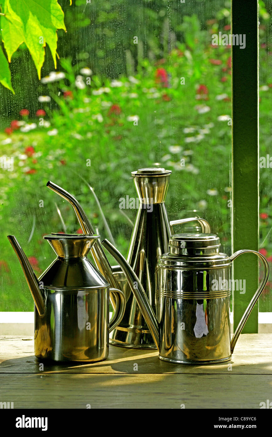 Cans of oil on a table on the terrace - Stock Image
